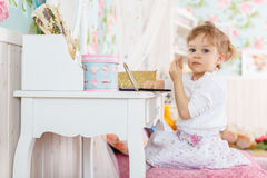 Little girl playing with cosmetics Royalty Free Stock Photography
