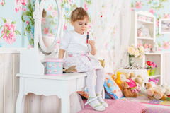 Little girl playing with cosmetics Royalty Free Stock Photo