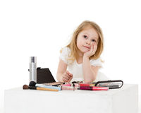 Little girl playing with cosmetics. Stock Photo