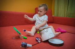 Little girl playing on the couch with makeup Stock Images
