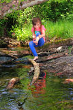 Little girl playing in a creek Stock Photo