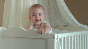 Little girl playing in the crib. FullHD video stock footage