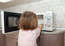 Little girl playing with dangerous kitchen appliance royalty free stock photo