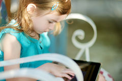 Little girl playing on a digital tablet Stock Photos