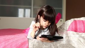 Little girl playing with digital tablet stock footage
