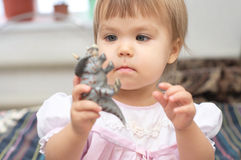 Little girl playing with dinosaur toy. Little girl playing with dinosaur Triceratops toy Royalty Free Stock Images