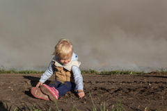 Little girl playing in the dirt. In front of a cloud of smoke Stock Images
