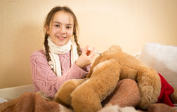 Little girl playing in doctor and doing injection to teddy bear Royalty Free Stock Images