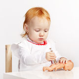 Little girl playing doctor with a doll Stock Image