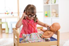 Little girl playing the doctor with her newborn baby doll in room royalty free stock photo