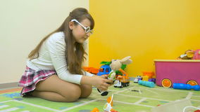 Little girl playing doctor with toys in the room. Little girl sitting on the floor and put on the glasses on face. She take a toy rabbit and start talking with stock video footage