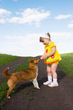 Little girl playing with a dog Royalty Free Stock Images
