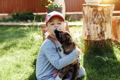 Little girl is playing with a dog. a dog as a gift to children. children`s smile on the nature Royalty Free Stock Photo