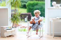 Little girl playing with doll Stock Image