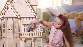 Little Girl Playing With A Dollhouse In Domestic Room Stock Footage