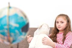 Girl playing with doll and map Globe royalty free stock image