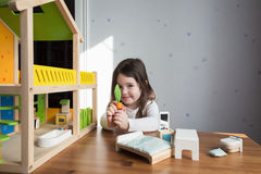 A little girl playing with dollhouse Stock Photography