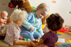 Little girl playing with dolls stock photos