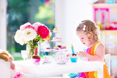Little girl playing with dolls Stock Image