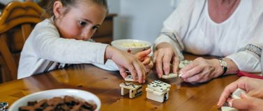 Little girl playing dominoes with mother and grandmother Stock Photos