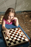 Little girl playing draughts board outdoor camping in the sunn Stock Photography