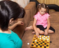 Little girl playing draughts with her mother royalty free stock images