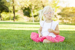 Little Girl Playing Dress Up With Pink Glasses and Necklace. Cute Little Girl Playing Dress In The Grass Up With Pink Glasses and Beaded Necklace stock photos