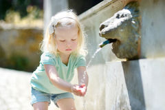 Little girl playing with drinking water fountain Royalty Free Stock Images