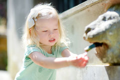 Little girl playing with drinking water fountain Royalty Free Stock Photos
