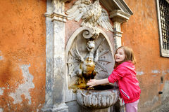 Little girl playing with drinking water fountain Royalty Free Stock Photo