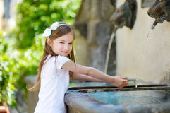 Little girl playing with a drinking water fountain Royalty Free Stock Photo
