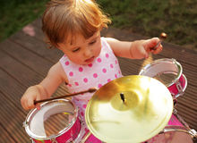Little girl playing drums Stock Images
