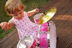Little girl playing drums stock photos