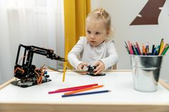 Little girl playing with electronic robot arm at home stock photography