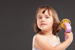 Little girl playing with fan Royalty Free Stock Photo