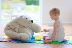 Little girl playing feeding her teddy bear Royalty Free Stock Photography