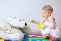 Little girl playing feeding her teddy bear Stock Photo