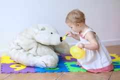 Little girl playing feeding her teddy bear Royalty Free Stock Images