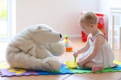 Little girl playing feeding teddy bear Stock Photography