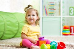 Little girl playing on floor at home or Royalty Free Stock Image