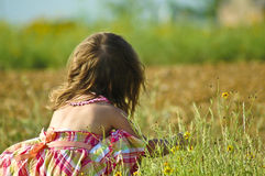 Little girl playing with flowers. A little girl playing with flowers in a field Stock Photos