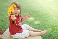 Little girl playing with flowers Royalty Free Stock Photography