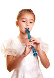 Little girl playing the flute Stock Photos