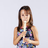 Little girl playing flute Royalty Free Stock Photos