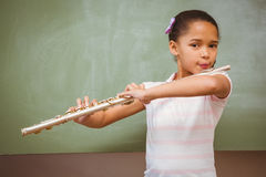 Little girl playing flute in classroom Stock Images