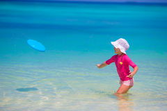 Little girl playing with flying disc at wnite Royalty Free Stock Image
