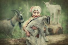 A little girl is playing in the forest with goats