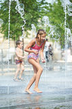 Little girl playing in a fountain Stock Photography