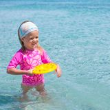 Little girl playing frisbee during tropical Stock Photo