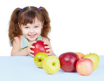 Little girl playing with fruits sitting at table Stock Image
